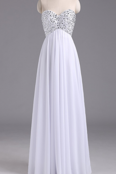 A sleeveless white long chiffon gown with a crystal and evening gown.